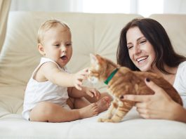 Mother and child playing with their pet cat