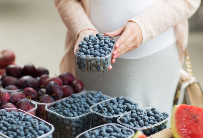 A pregnant woman picking blueberries in a market