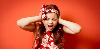 Little girl covering her ears, looking troubled