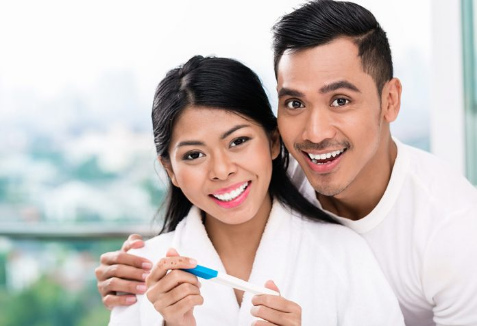 A woman with her husband, smiling while seeing results of the pregnancy test