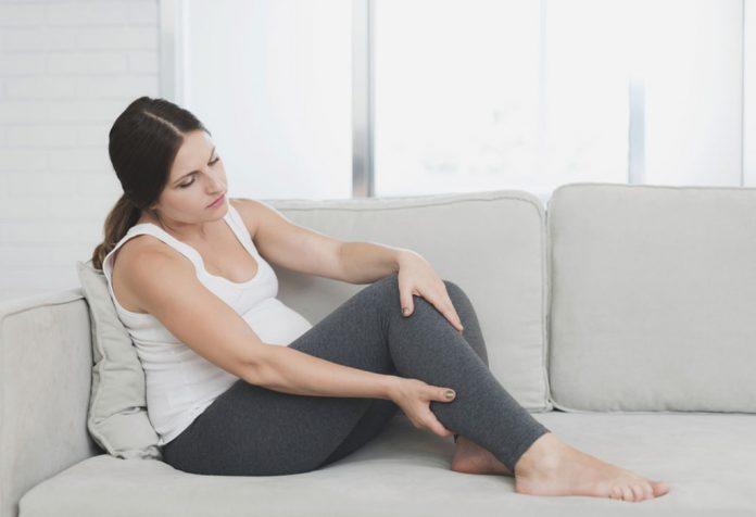 Woman massaging leg