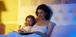 A mother and daughter reading a book together in bed