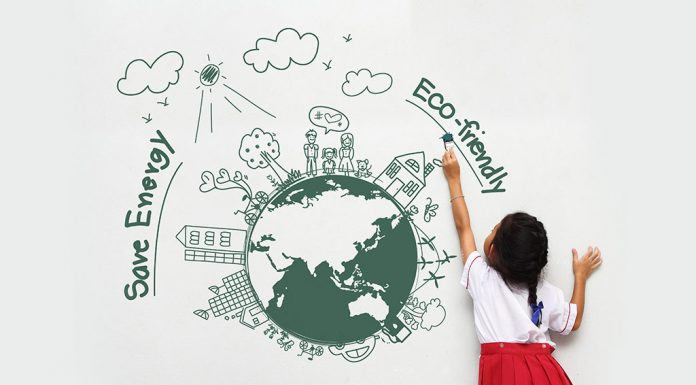 A little girl drawing a creative of the Earth on a wall