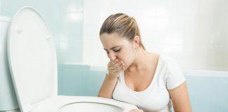 A pregnant woman sitting in a bathroom, feeling sick