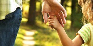 A father holding his daughter's hand
