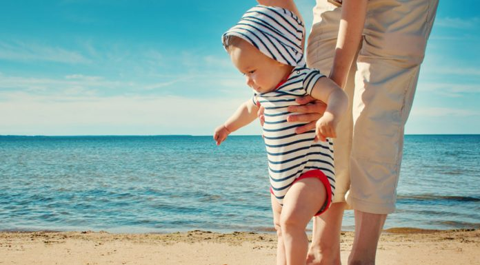 A nine month-old baby walking on the beach