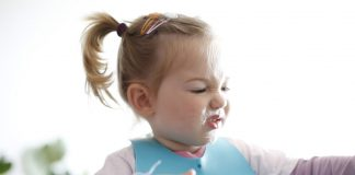 A little girl making faces while eating