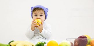 A baby surrounded by fruits and vegetables