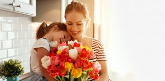 A little girl giving a bouquet of flowers to her mother