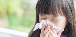 A little girl sneezing because of an allergy