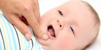 A baby smiling an showing its first few teeth