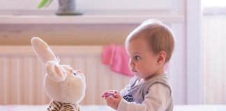 A 10 month-old baby playing with a bunny