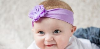 A baby girl wearing a purple hairband
