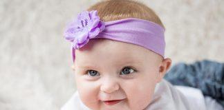 A baby girl wearing a purple hairband