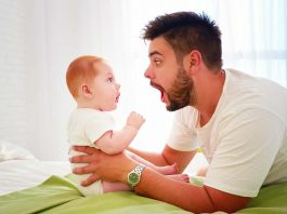 A baby looking at his father