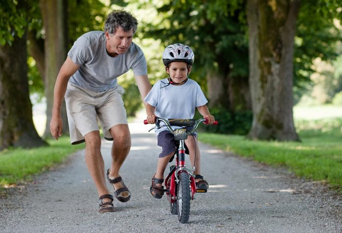 CHILD LEARNING TO RIDE A BICYCLE